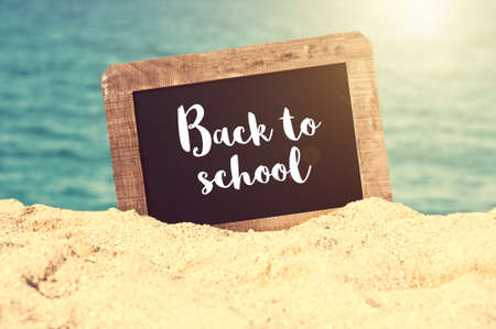 Back to school written on a vintage chalkboard in the sand of a beach Banque d'images