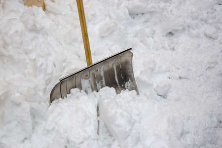 Metallic snow shovel stuck in the snow after a storm