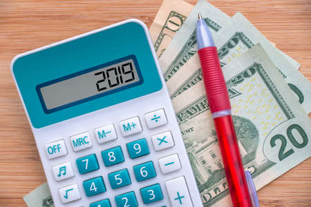 2019 written on a calculator and dollars banknotes on wooden background