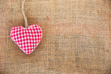 Red fabric heart on rustic canvas background