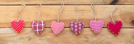 Line of red fabric hearts hanging on old wood background