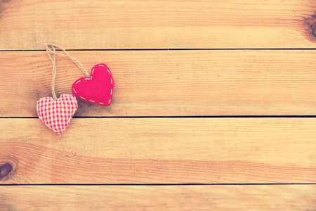 Two red fabric hearts on old wood background, vintage process