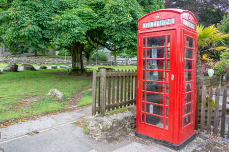 Red traditional english Phone booth in Widecombe in the Moor, Devon, UK
