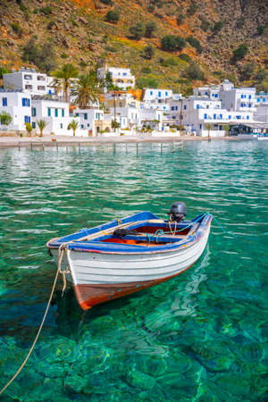 Fishing boat and the scenic village of Loutro in Crete, Greece Фото со стока