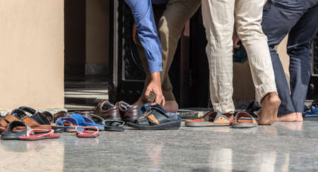 Men removing shoes at the entrance of a mosque in Dubai, United Arab Emirates