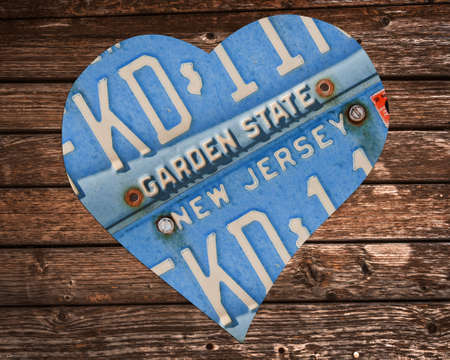 New Jersey state license plates in the shape of a heart on wood background