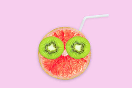 Fruit creative face with slices of grapefruit and kiwi, drinking straw on pink background, fruit juice and summer concept