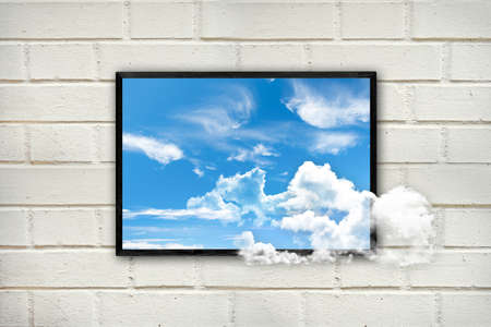 Frame with clouds and blue sky on a white brick wall, thinking outside the box concept Stock Photo