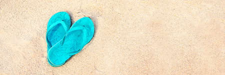 Blue pair of flip flops on the beach, panoramic summer concept Stock Photo