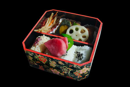Square japanese bento box with rice and vegetables, isolated on black background Stock Photo