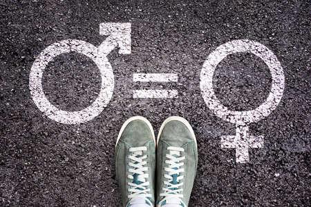 Sneaker shoes on asphalt background with gender symbols, gender equality education concept Stock Photo
