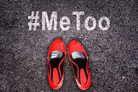 Red high heels shoes on asphalt, hashtag Metoo