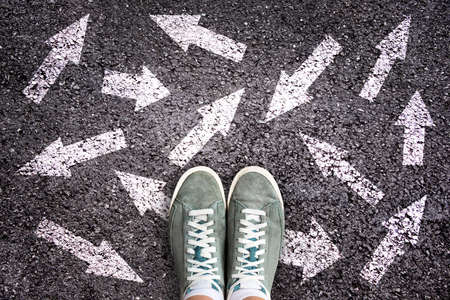 Sneaker shoes and arrows pointing in different directions on asphalt ground, choice concept Archivio Fotografico