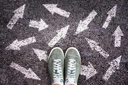Sneakerschoenen en pijlen die in verschillende richtingen op asfaltgrond wijzen, keusconcept
