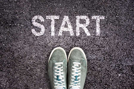 Sneaker shoes and the word START written  on asphalt ground, new life concept