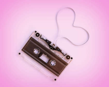 Translucent audio cassette with the magnetic tape in the shape of a heart  isolated on pink background, music love concept