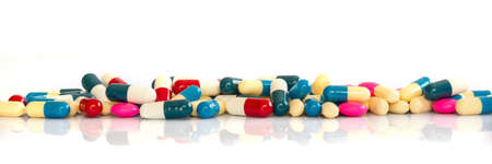 Line of colorful pills and medication on white background with copy space, health and medication concept