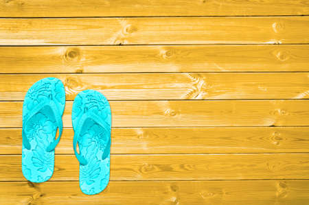 Blue flip flops on yellow planks, summer concept background with copy space