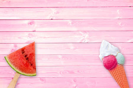 Watermelon ice and ice cream cone on pink planks background with copy space, summer concept