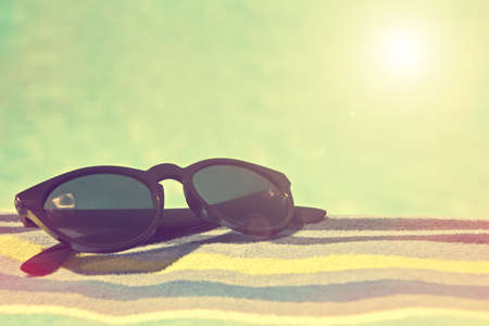 Black sunglasses on a bath towel, vintage summer concept