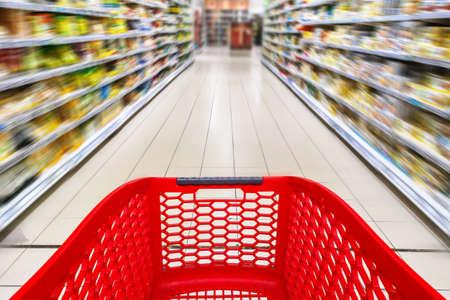 Carrello della spesa vuoto rosso in un corridoio del supermercato, sfocatura del movimento motion