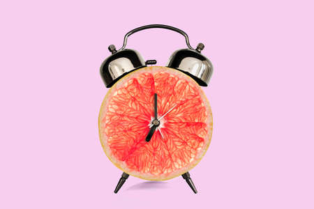 Grapefruit slice on alarm clock, pink pastel background. fruit and vitamins diet at breakfast nutrition concept Stockfoto