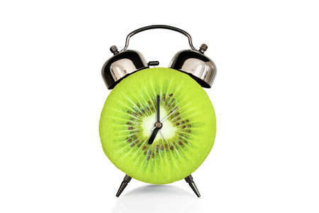 Kiwi slice on alarm clock, isolated on white background, fruit and vitamins diet at breakfast nutrition concept