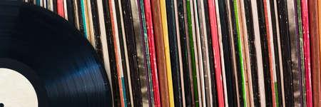 Vinyl-Schallplatte vor einer Sammlung von Alben, Vintage-Musikkonzept