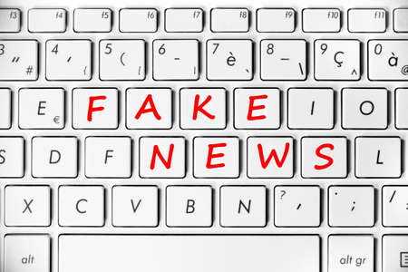 Fake news written on a computer keyboard background