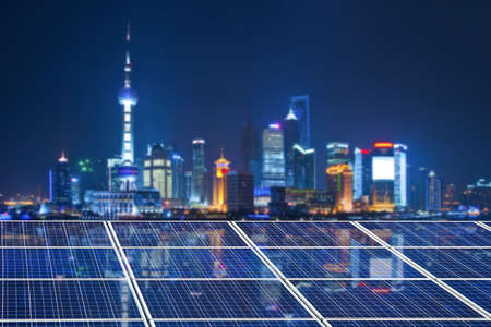 Blue solar cell panels,Shanghai skyline illuminated at night in the background