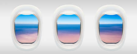 Windows of airplane from inside, blue sky and pink clouds, aerial travel concept Stock Photo