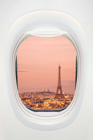 Paris at sunset seen through the window of airplane, travel in Europe concept