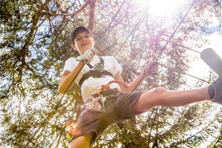 Teenager with action camera having fun on high ropes course, adventure park, climbing trees in forest in summer