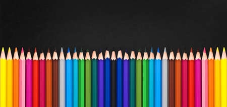 Row of colorful wooden pencils on blackboard background with copy space, back to school concept