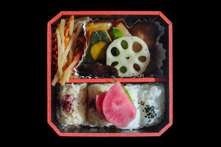 Top view of a square japanese bento box with rice and vegetables, isolated on black background Stok Fotoğraf