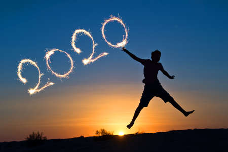 2020 written with sparkles, silhouette of a boy jumping in the sun, holiday card