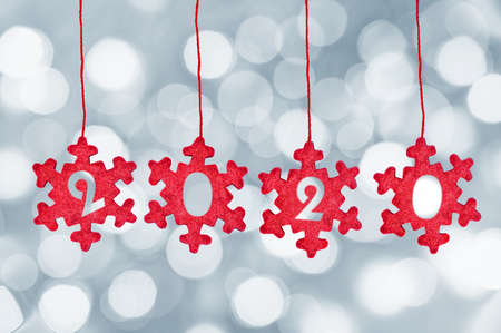 2020 cut in red fabric christmas ornaments hanging on bokeh lights background