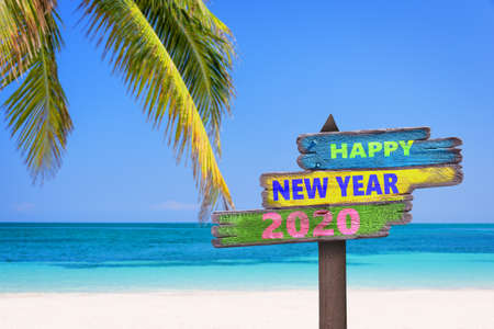 Hapy new year 2020 on a colored wooden direction signs, beach and palm tree background