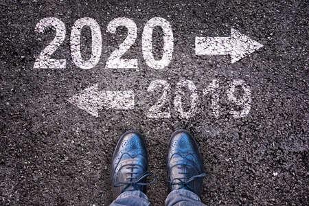 2020 en 2019 met richtingspijlen geschreven op een asfaltwegachtergrond met benen