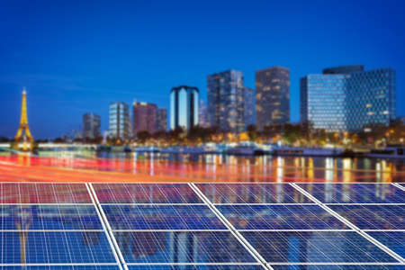 Blue solar cell panels, Paris cityscape illuminated at night in the background Banco de Imagens