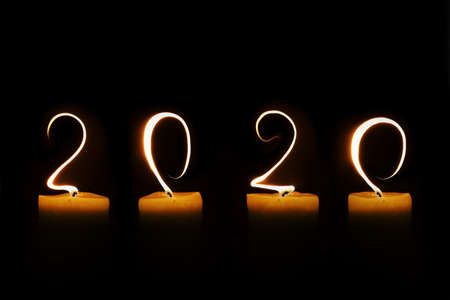 2020 written with candle flames on black background, greeting card