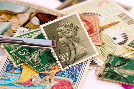 Tweezers holding a UK postage stamp with Queen Elizabeth 2 side portrait. Collections of stamps in the background.