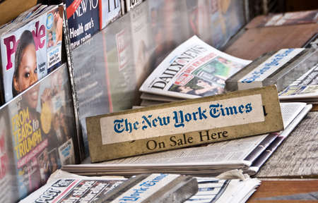 The New York Times, on sale here board with other magazines and newspapers in New York, USA