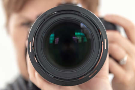 Close up of a DSLR camera lens, blurred hands of woman professional photographer Фото со стока