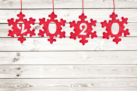 2020 cut in red fabric christmas ornaments hanging on white planks background