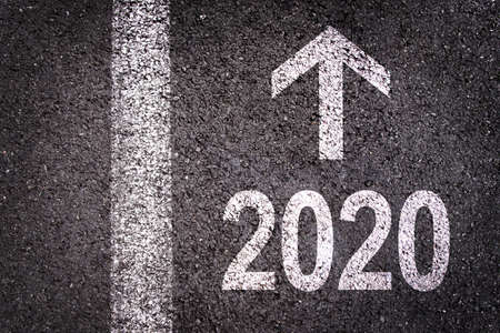2020 and a direction arrow written on an asphalt road background, urban new year greeting card Stock fotó