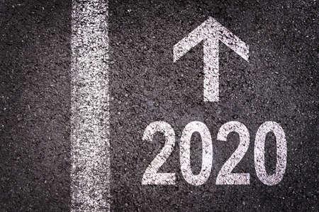 2020 e una freccia di direzione scritta su uno sfondo di strada asfaltata, biglietto di auguri per il nuovo anno urbano Archivio Fotografico