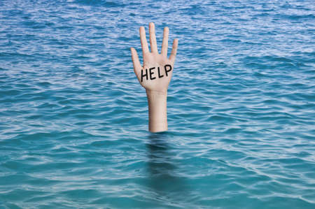 Word help written on the palm of a sinking hand in oceans water. Drowning person Emergency, failure and help concept