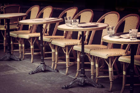 Empty retro tables and chairs on a outdoor cafe terrace in Paris, France