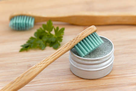 Bamboo toothbrushes and solid toothpaste in metal tin on wood background. Zero waste, plastic free, environment concept Banco de Imagens